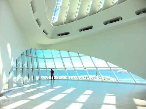 In a large sunlit hall with curving white walls, a silhouetted figure faces away toward blue sea and sky