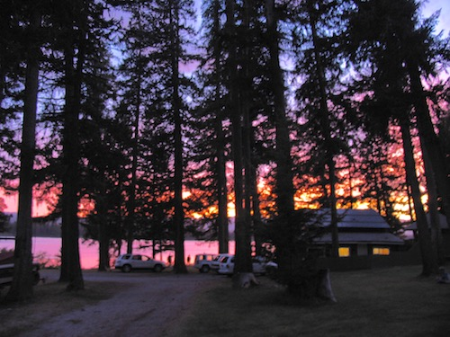 Tall evergreens and a cabin with lighted window silhouetted against a colorful sunset beyond a lake